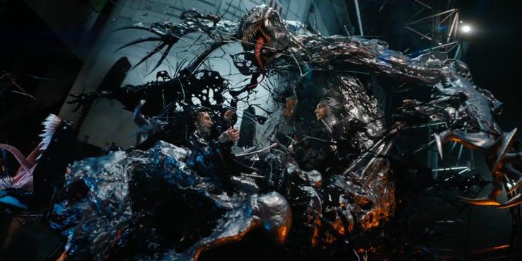 Riot (widoczny z prawej strony zdjęcia) - wiemy już, że w filmie będzie on mógł przeskakiwać z gospodarza na gospodarza; w zwiastunie widzimy kilka zmian w stosunku do komiksów - ostrza Riota przypominają raczej broń innego symbionta, Phage'a, a jego szaro-niebieska barwa została zastąpiona srebrno-czerwoną